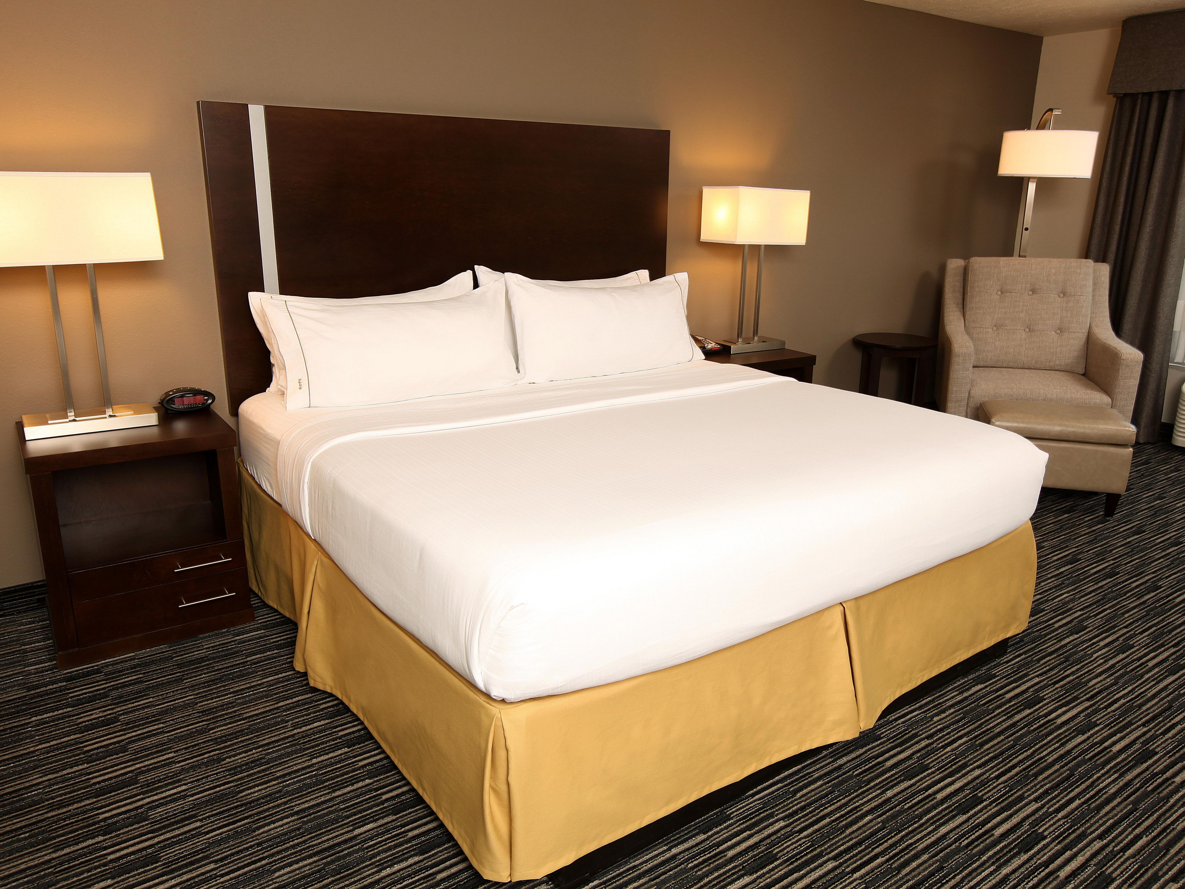 Comfortable king size bed and well-lit soft seating area.