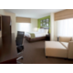 Corner queen suite with chair and ottoman and a walk in shower.