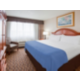 2 room suite with a king bed and breakfast table with 4 chairs